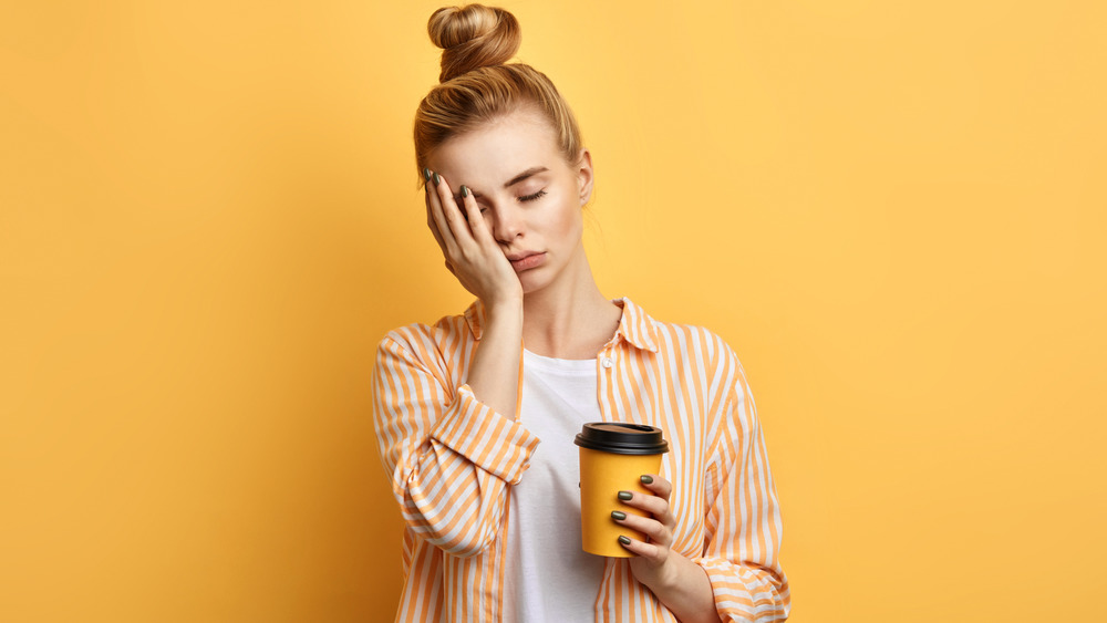 Woman tired and holding coffee