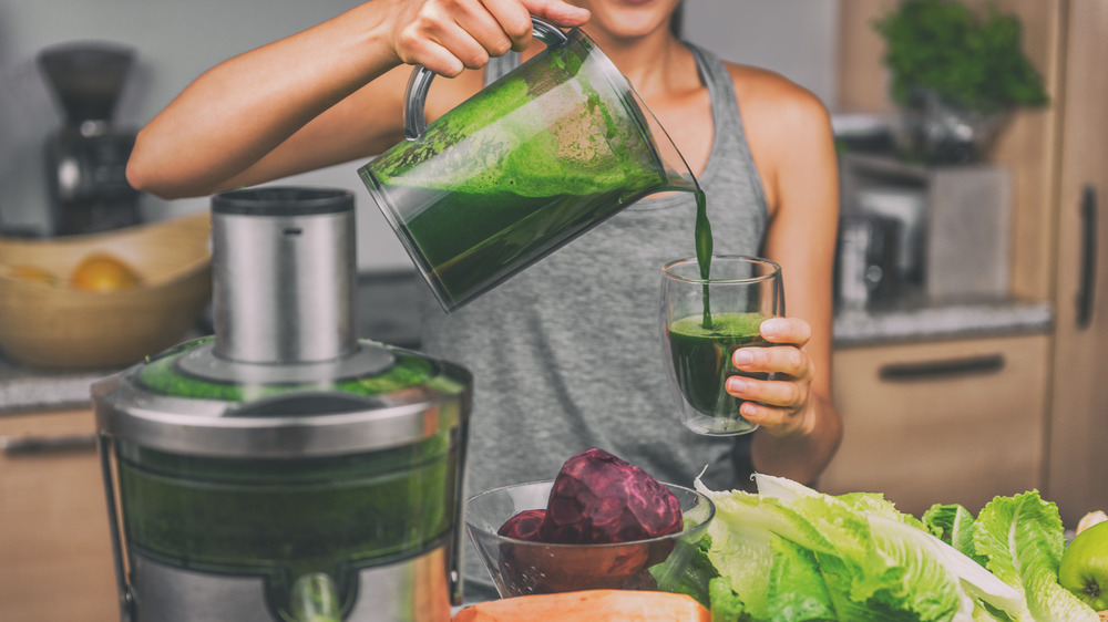 woman pouring green juice