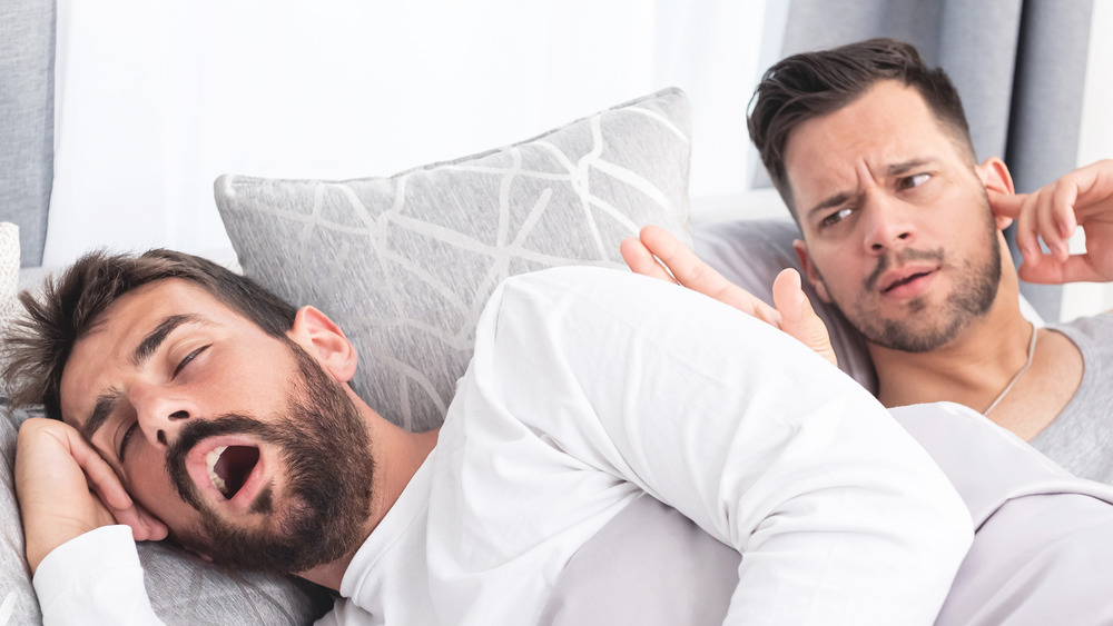 two men in bed, one with mouth open and the other plugging his ear