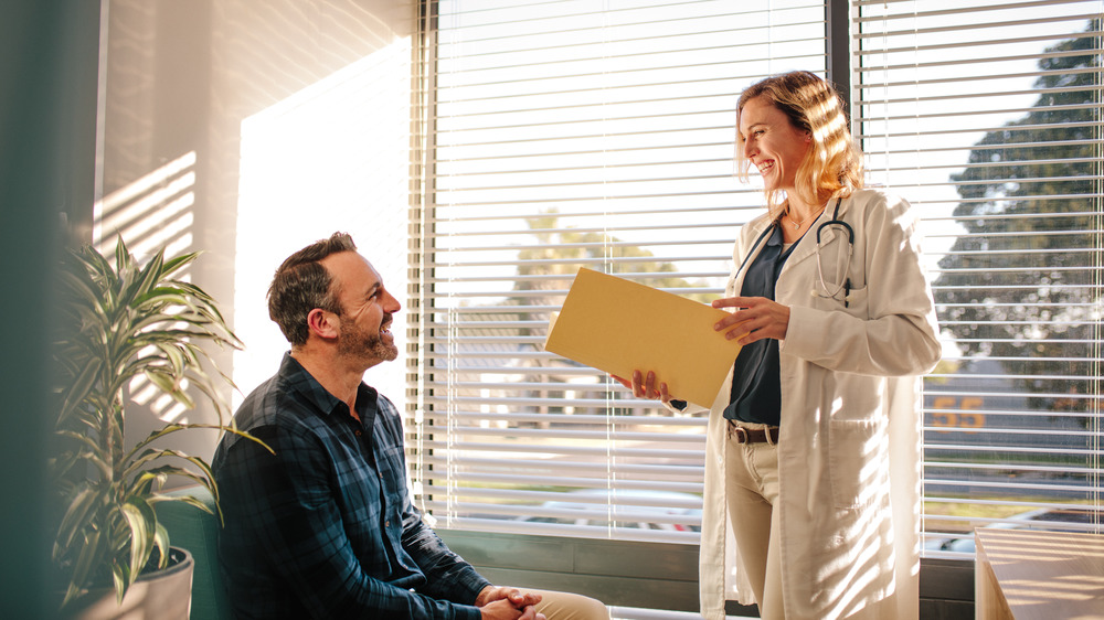 Doctor smiling at her patient next to an open window
