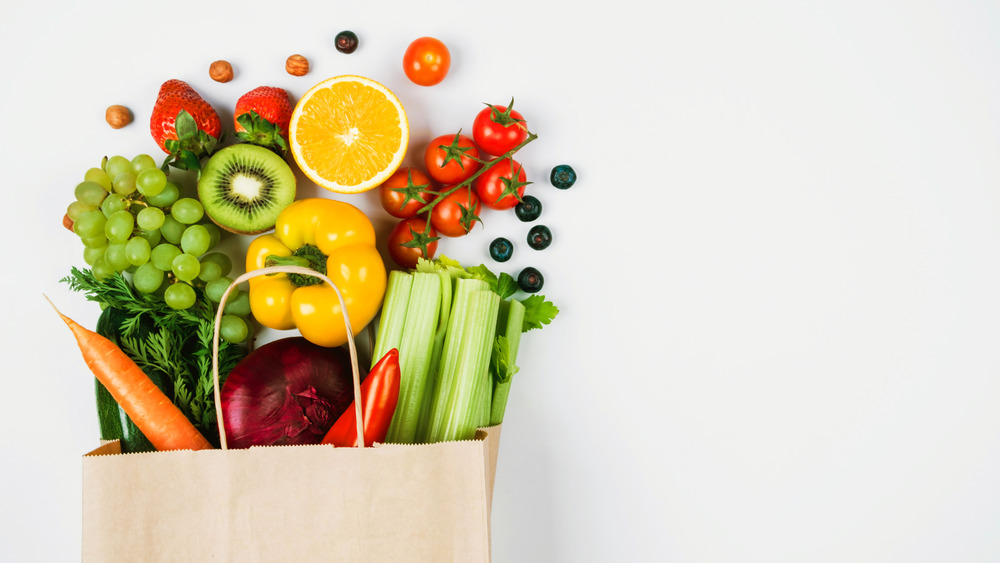 Fruits and vegetables spilling out of a grocery bag