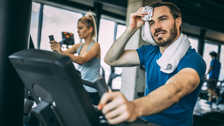 Cycling man, wiping away sweat from brow