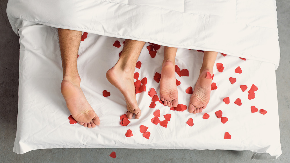 Couples feet in bed under covers